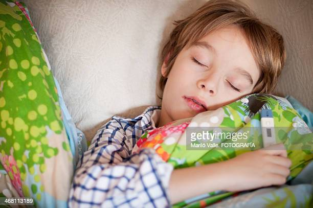 boy sick with thermometer in hand