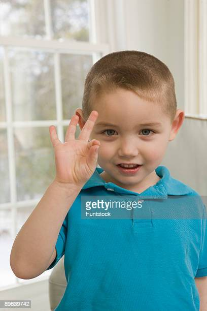 Boy signing the letter 'F' in American sign language