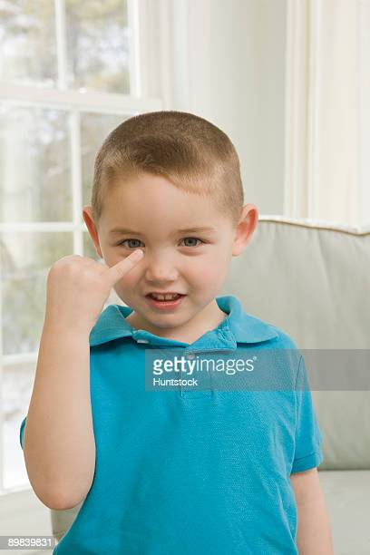 Boy signing the letter 'J' in American sign language