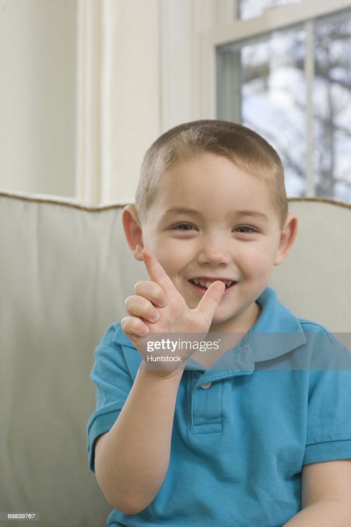 Boy signing the letter 'L' in American sign language : Photo
