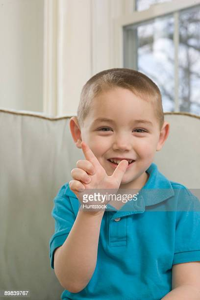 Boy signing the letter 'L' in American sign language