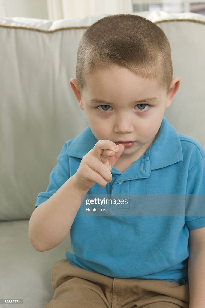 Boy signing the letter 'R' in American sign language