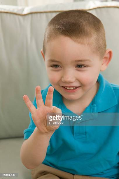 Boy signing the number '9' in American sign language
