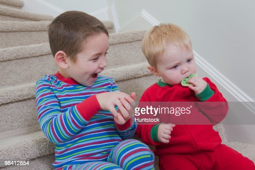 Boy signing the word 'Cookie' in American Sign Language while communicating with his brother : Foto de stock