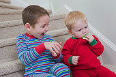 Boy signing the word 'Cookie' in American Sign Language while communicating with his brother