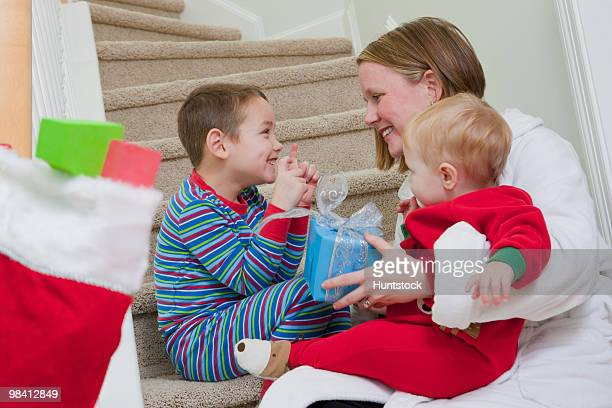 Boy signing the word 'Present' in American Sign Language while communicating with his mother