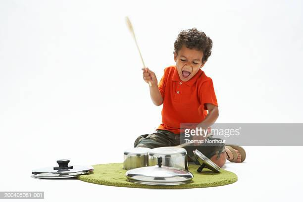 Boy (4-6) singing and hitting pans with drumsticks (blurred motion)