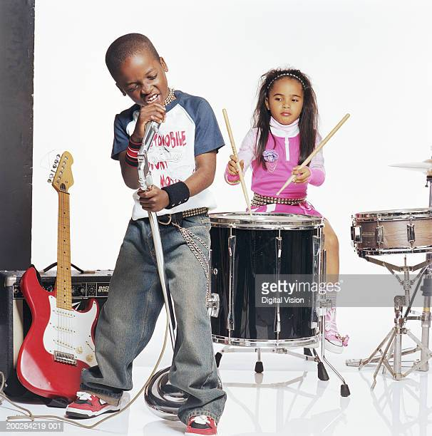 Boy (9-11) singing into microphone by girl (7-9) playing drums