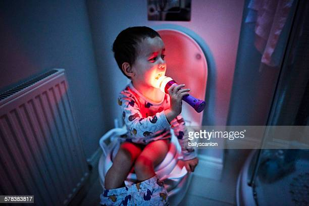 Boy singing into microphone on toilet