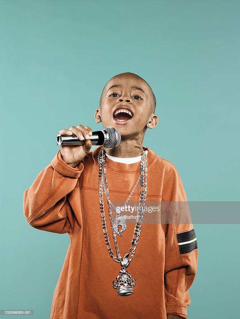 Boy (4-6) singing on microphone