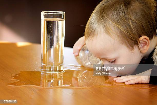 Boy sipping water from table