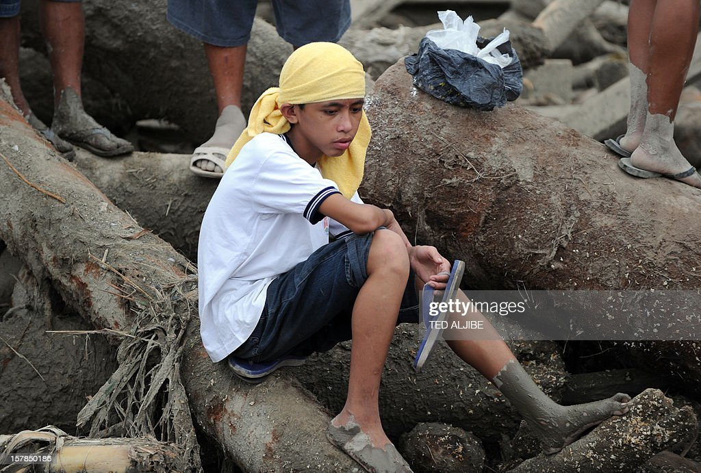 A boy sits amongst debris swept away by flash floods at the height Typhoon Bopha as he waits for word of missing relatives in New Bataan, Compostela Valley province on December 7, 2012. President Benigno Aquino vowed action on the Philippines' typhoon disasters December 7 as bruised and grieving survivors tried to recover from the latest that left nearly 500 people dead