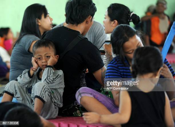 A boy sits behind his parents and villagers after being evacuated during the raised alert levels for the volcano on Mount Agung in Klungkung regency...