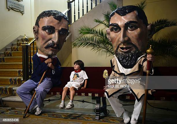 A boy sits between two 'Cabezudos' at the City Hall of Pamplona northern Spain on July 14 2015 during the last day of the San Fermin Festival The...