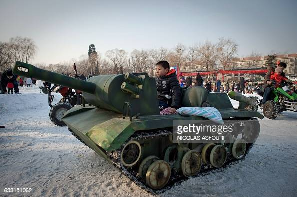 A boy sits in a tank at an amusement fair in a park during the Spring Festival holidays in Beijing on January 31 2017 Millions of Chinese are...