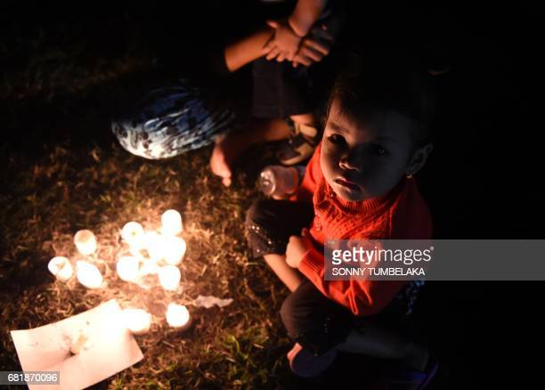 A boy sits in front candles in support for Basuki Tjahaja Purnama known by his nickname Ahok to give their support for his freedom from the accused...