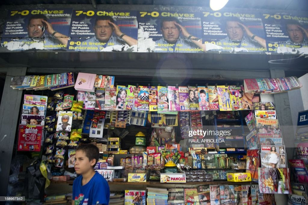 A boy sits in front of a kiosk decorated with posters of Venezuelan President Hugo Chavez in Caracas on January 4, 2013. Hugo Chavez's top aides have gone on the offensive, accusing the opposition and media of waging a 'psychological war,' as Venezuela's cancer-stricken president battles a serious lung infection. The closing of ranks followed a high-level gathering of top Venezuelan officials in Havana with Chavez, amid growing demands to know whether he will be fit on January 10 to take the oath of office for another six-year-term. AFP PHOTO/Raul ARBOLEDA