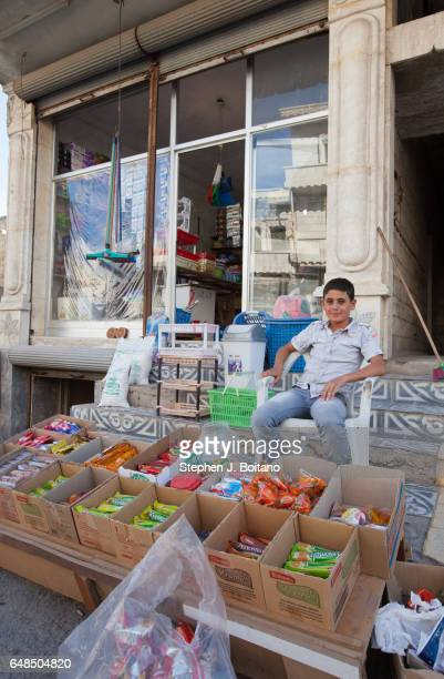 A'ZAZ ALEPPO SYRIA A boy sits in front of a shop in downtown in A'zaz Syria