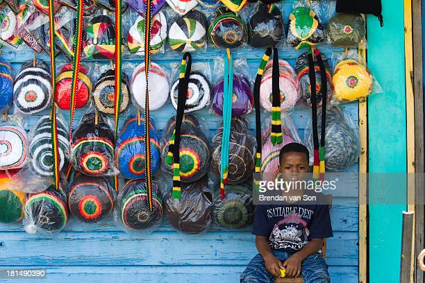 CONTENT] A boy sits in front of a stall selling rasta hats in Jamaica