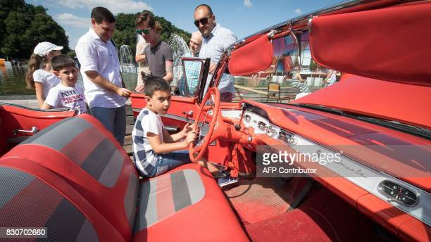 A boy sits inside of a classic automobile during the Faces and Laces alternative modern art festival on August 12 2017 in the Gorky Central Park of...