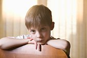 Boy sits looking at camera, leaning on chair back