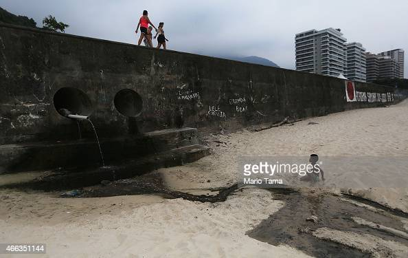 A boy sits near a pipe draining polluted water on Sao Conrado beach on March 14 2015 in Rio de Janeiro Brazil Brazil's inflation rate has hovered...