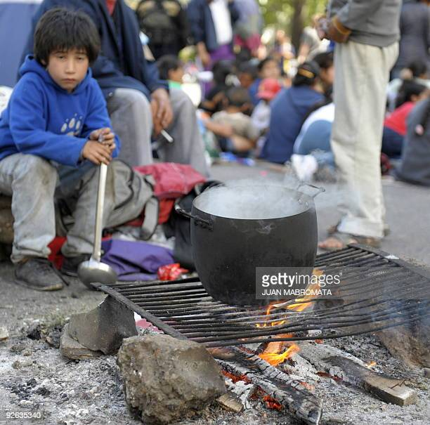 A boy sits next to a pot with boiling water to brew mate during a picket by members of social organizations of the poor and unemployed who demand to...