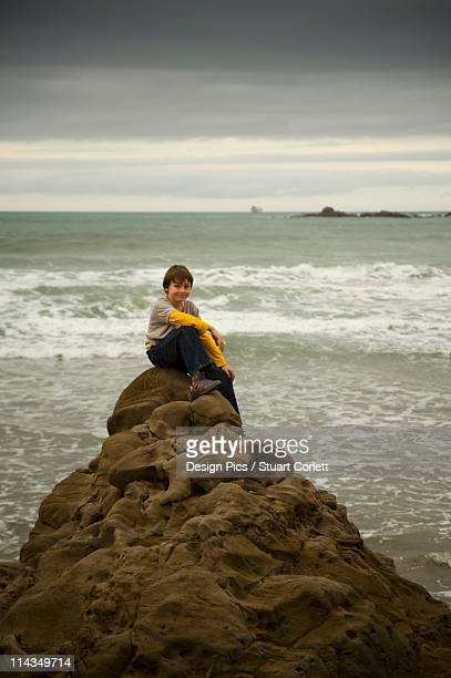 A Boy Sits On A Rock At The Water's Edge