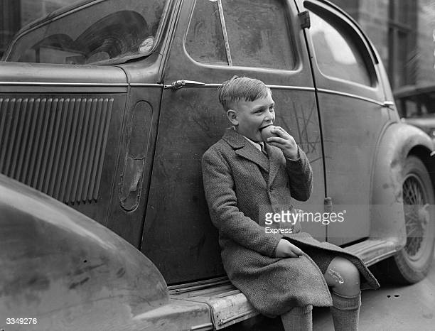 A boy sits on the running board of a car eating an apple