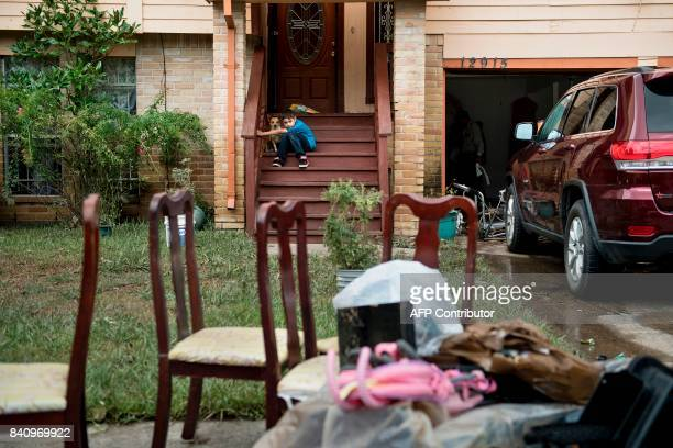 A boy sits with a dog as belongings are salvaged after flood waters receded during the aftermath of Hurricane Harvey on August 30 2017 in Houston...