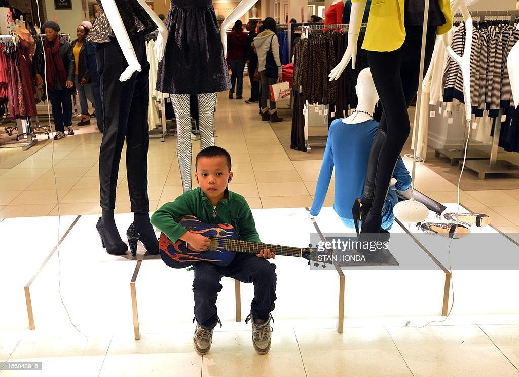 A boy sits with a toy guitar on a display in Macy's department store after the store opened at midnight (0500 GMT) on November 23, 2012 in New York to start the stores' 'Black Friday' shopping weekend. AFP PHOTO/Stan HONDA