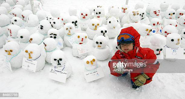 A boy sits with snowmen during the 60th Sapporo Snow Festival on February 5 2009 in Sapporo Japan The 60th Sapporo Snow Festival takes place from...