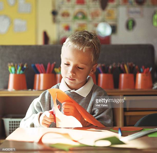 Boy (6-8) sitting at desk, cutting paper with scissors