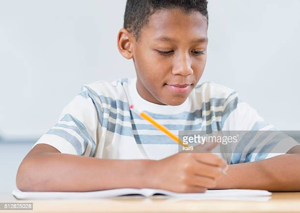 Boy sitting at desk in class writing in notebook
