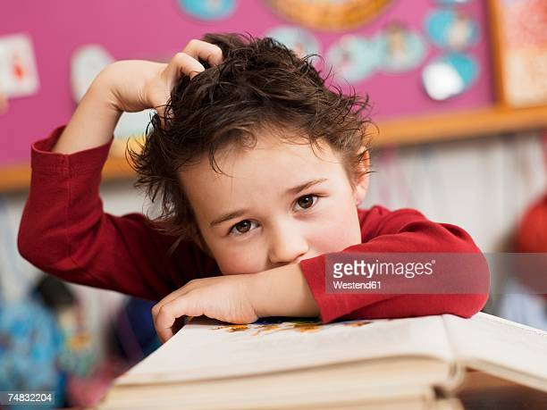 Boy (4-5) sitting at desk with book, hand in hair, portrait, close-up