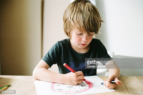 Boy sitting at table and drawing