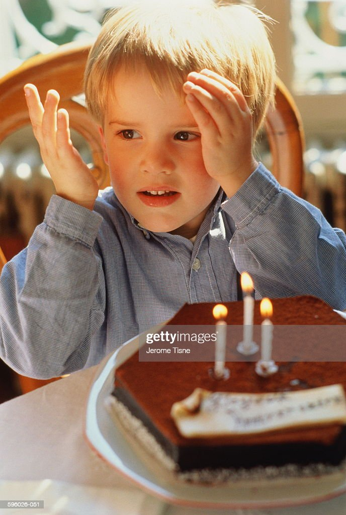 Boy (3 years) sitting at table in front of birthday cake : Stock Photo