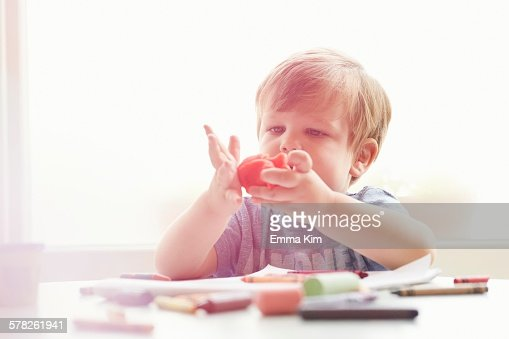 Boy sitting at table with art supplies playing with modelling clay