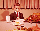 Boy sitting  at table with hands folded for grace prayer, looking at roast turkey. (Photo by H. Armstrong Roberts/Retrofile/Getty Images)