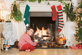 Boy sitting by fireplace at Christmas