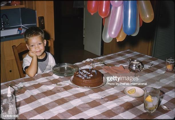 Boy sitting by table