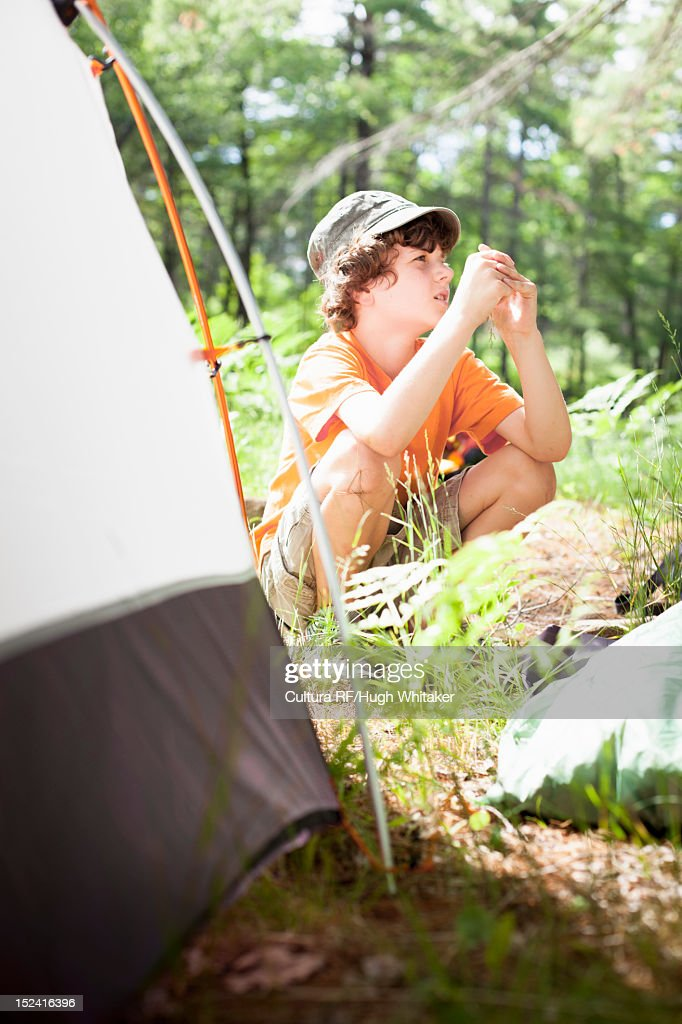 Boy sitting by tent at campsite : Stock Photo
