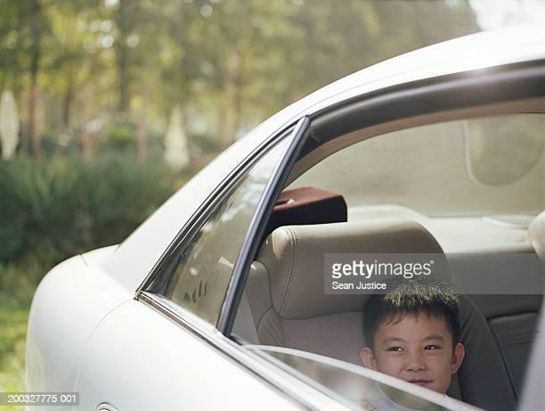 Boy (4-6) sitting in back seat of car