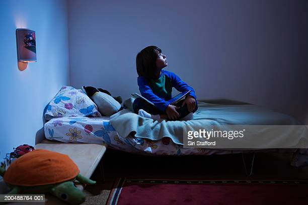 Boy (8-10) sitting in bed, looking up