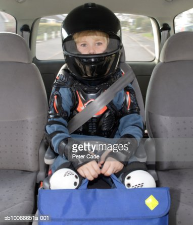 Boy (6-7) sitting in car wearing helmet