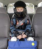 Boy (6-7) sitting in car wearing helmet