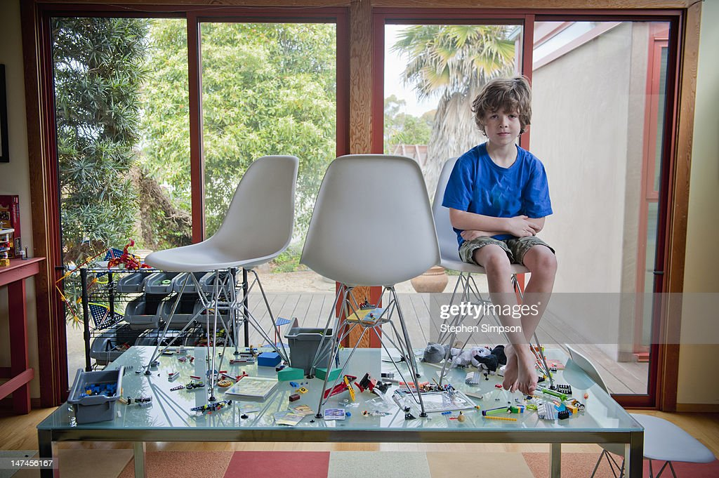 boy sitting in chair on table covered with toys : Stock Photo