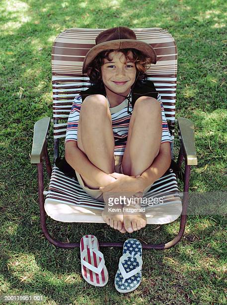 Boy (6-8) sitting in deckchair, hands around ankles, portrait