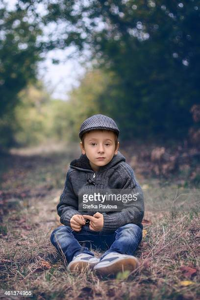 Boy sitting in forest