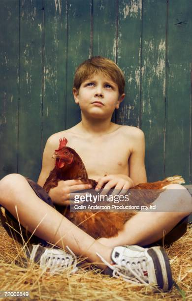 Boy sitting in hay with chicken in his lap